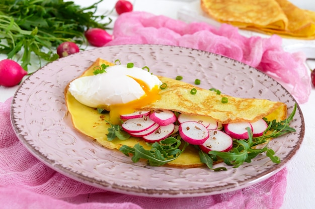 French breakfast radish salad and arugula, egg poached on a thin crape