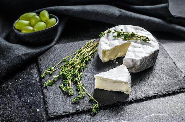ブドウとフランスのブリーチーズ。黒の背景。上面図。