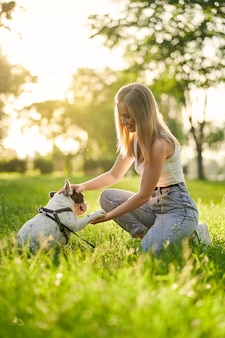 French bulldog giving paw to female owner in park