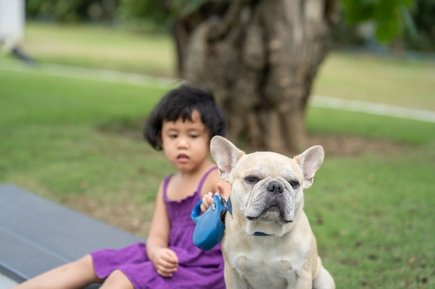 French bulldog sitting on bench with little girl in violet dressed