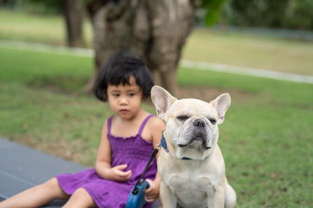 보라색 옷을 입은 어린 소녀와 벤치에 앉아 프랑스 불독