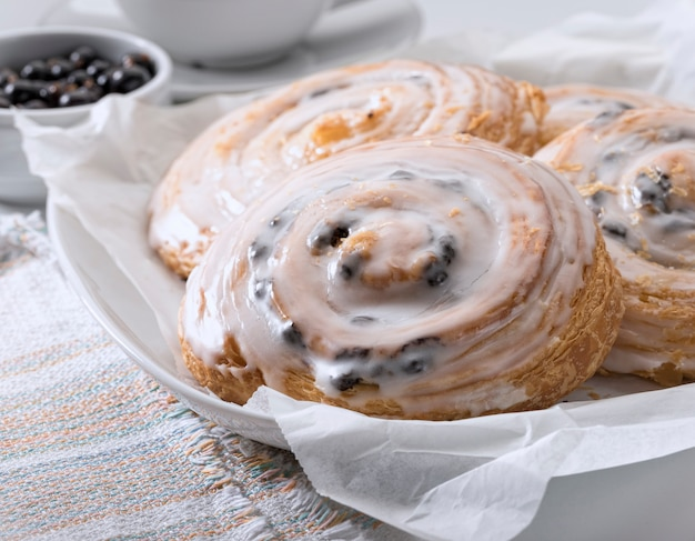 French buns with cinnamon and raisins on a white plate.