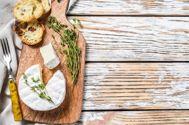 木製のまな板にブドウとフランスのカマンベールチーズ。白色の背景。上面図。スペースをコピーします。