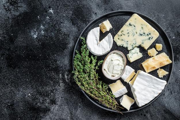 프랑스 치즈 플레이트. 카망베르, 브리, 고르곤 졸라, 블루 크림 치즈. 검정색 배경. 평면도. 공간을 복사하십시오.