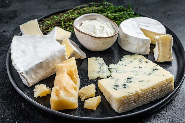 Французская сырная тарелка. камамбер, бри, горгонзола и сливочный сыр с голубой плесенью. черный фон. вид сверху.