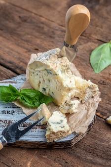フランスのチーズブルーチーズドルブル、ゴルゴンゾーラ、木製テーブルのロックフォール。垂直方向の画像。上面図。テキストの場所。