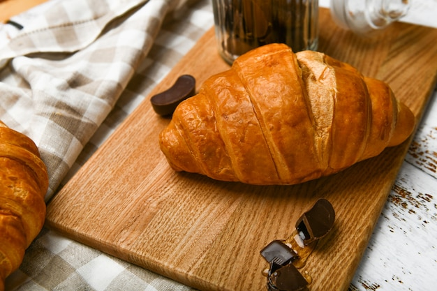 French chocolate croissants top view. the beginning of the morning. fresh french croissant. coffee cup and fresh baked croissants on a wooden . .