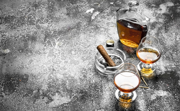 French cognac with a cigar. on a rustic background.