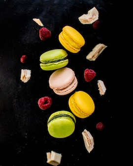 French colorful macarons in motion with white chocolate and raspberries