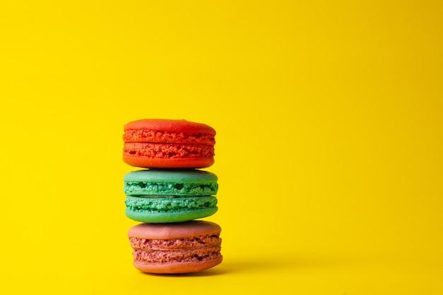 Французские красочные macarons на желтом