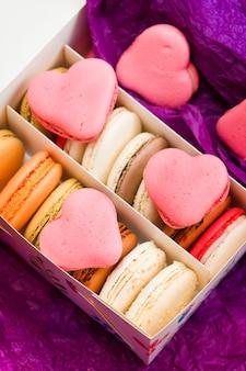 Французские разноцветные макаруны с сердечками на фиолетовом фоне