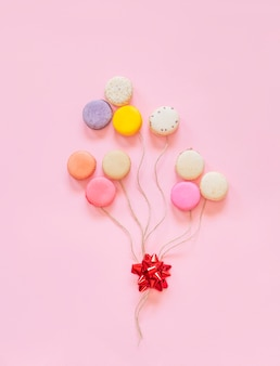 French colorful macaroons cakes in form of balloons isolated on pink background.