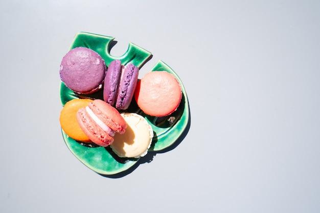 灰色の背景、上面図上のリーフプレート上のフランスのクッキーマカロン