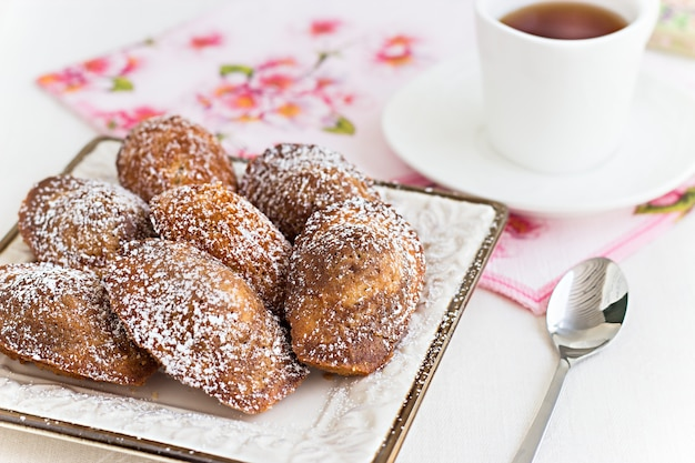 French cookies madeleine and tea in white cup. concept romantic breakfast.