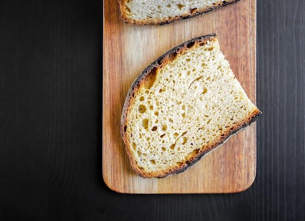 Кусочки французского деревенского хлеба на деревянной разделочной доске