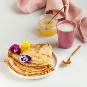 花で飾られたフランスのクレープパンケーキカプチーノのマグカップと朝食の蜂蜜のコンセプト...