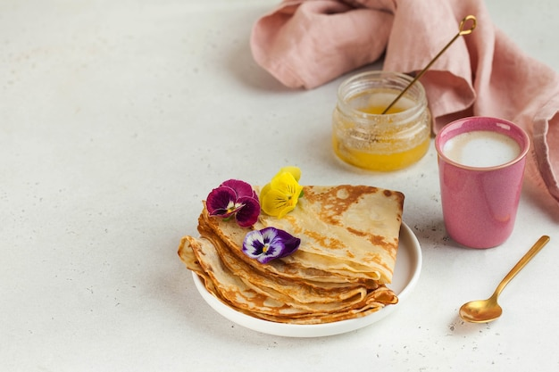 French crepes pancakes decorated with flowers a mug of cappuccino and honey concept of breakfast des...
