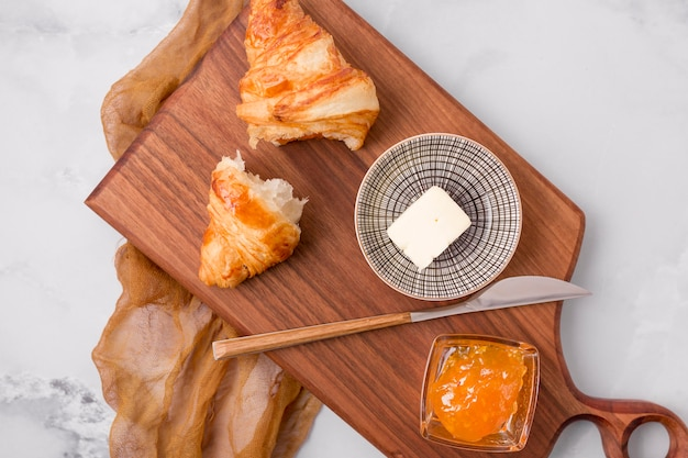 French croissant breakfast and jam on cutting board