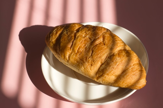 French croissant on plate on table with hard shadow from blinds.