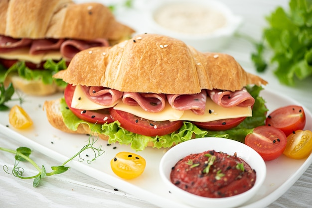 French croissant with ham, cheese, tomato and salad
