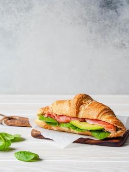 Французский круассан с ломтиками лосося, авокадо и шпинатом на деревянной доске. копировать пространство