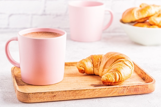 French croissants and cup of coffee  on a wooden tray.