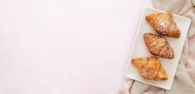 Croissant francesi in uno spazio della copia del piatto
