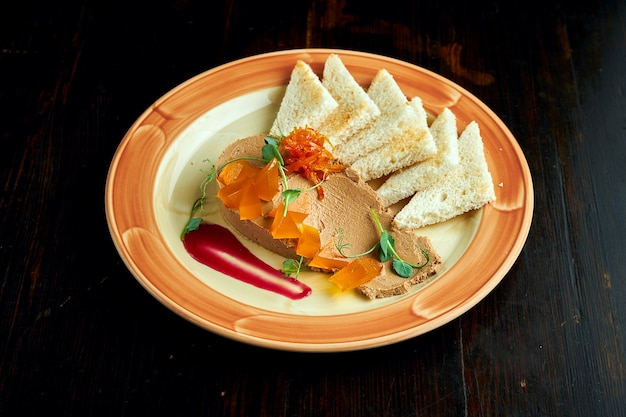 French cuisine appetizer - chicken liver pate with onion confiture, white croutons, served in a plate on a dark wood background.