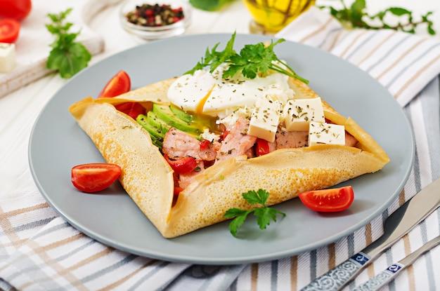 Cucina francese. colazione, pranzo, spuntini. pancake con uovo in camicia, formaggio feta, prosciutto fritto, avocado e pomodori sulla tavola bianca