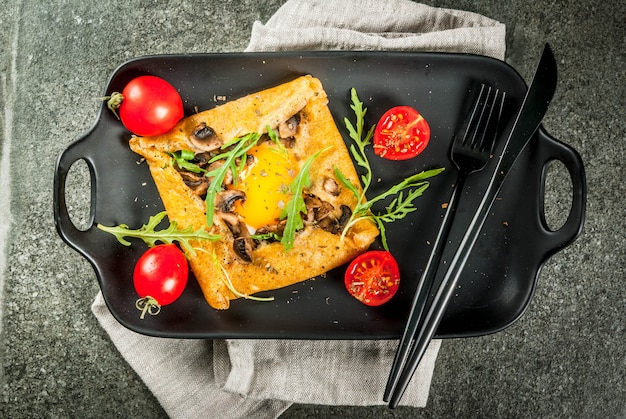 French cuisine breakfast lunch snacks vegan food traditional dish galette sarrasin crepes with eggs cheese fried mushrooms arugula leaves and tomatoes on black stone table