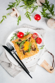 French cuisine breakfast lunch snacks vegan food traditional dish galette sarrasin crepes with eggs cheese fried mushrooms arugula leaves and tomatoes