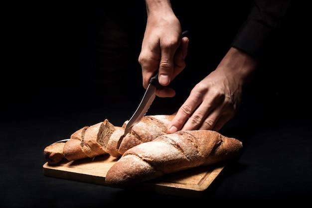 프랑스 요리. 닫기 바게트를 자르고 레스토랑에서 요리사로 일하는 동안 요리하는 젊은 남자의 손을 닫습니다.
