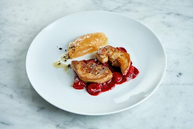 フランス料理-フォアグラのレバーのグリル、ベリーソースとアップルピューレ、大理石のテーブルの白いプレートでお召し上がりいただけます