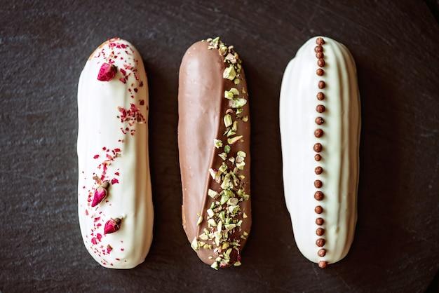 黒い石のプレートにチョコレートのアイシングとさまざまなトッピングを添えたフランスのデザートエクレアまたはプロフィットロール。クリームとペストリーカスタードケーキ。ソフトセレクティブフォーカス。