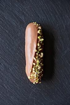 검은 돌 접시에 밀크 초콜릿 글레이즈와 피스타치오를 곁들인 프랑스 디저트 eclairs 또는 profiteroles. 크림과 토핑 케이크. 소프트 선택적 초점.