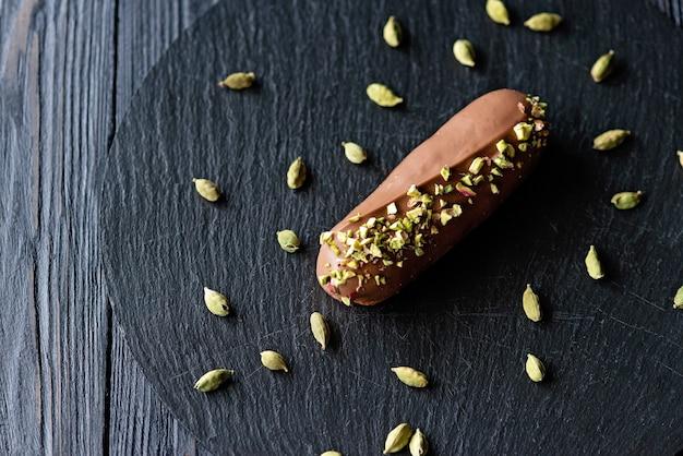 카 다몬과 피스타치오로 맛을 낸 밀크 초콜릿 유약을 곁들인 프랑스 디저트 eclairs 또는 profiteroles. 피스타치오 크림과 토핑을 곁들인 케이크. 소프트 선택적 초점.