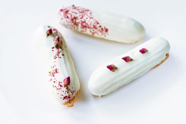 프랑스 디저트 eclairs 또는 흰색 배경에 장미 맛 화이트 초콜렛 유약을 가진 profiteroles. 커스터드, 로즈 크림 및 토핑을 곁들인 페이스트리 케이크. 소프트 선택적 초점.