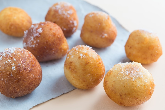 French doughnuts beignet covered with sugar powder on a brown