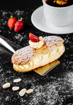 French eclair dessert with whipping cream and strawberries.