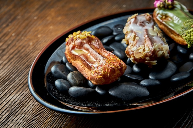 カスタードと各種トッピングのフレンチエクレアを木製の背景の黒いプレートに添えました。レストランの食べ物。