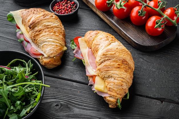 아침식사로 프랑스 음식. 검은색 나무 테이블 배경에 허브와 재료를 넣은 햄 그린과 치즈 세트를 곁들인 구운 크루아상 샌드위치