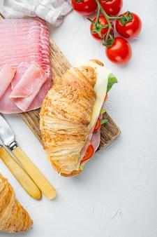 朝食にフランス料理。焼きクロワッサンサンドイッチ、ハムグリーンとチーズのセット、ハーブと材料、白い石のテーブル、上面図フラットレイ