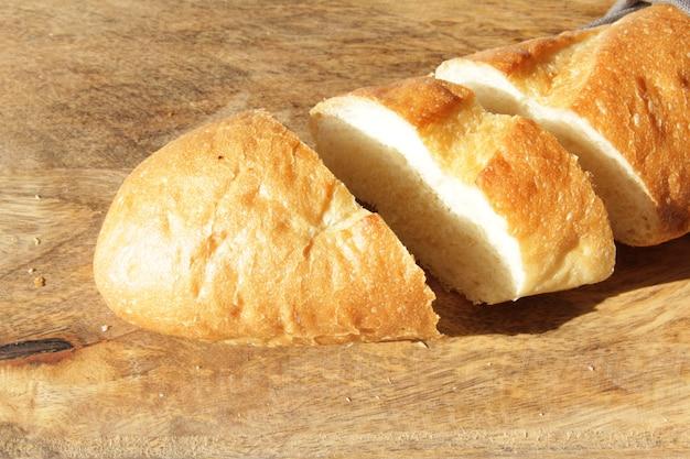 木製のまな板にフランスの焼きたての柔らかいパンのバゲット