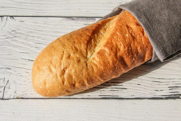 ナプキンと木製の背景にフランスの焼きたての柔らかいパンのバゲット