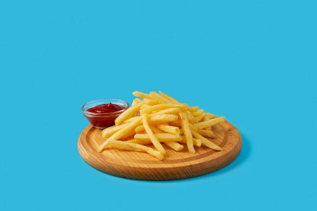 Картофель фри и соус кетчуп на разделочной доске меню ресторана кафе