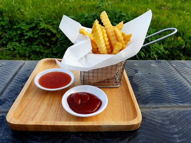French fries in the basket with chili and tomato sauce on a wooden plate by grass field background