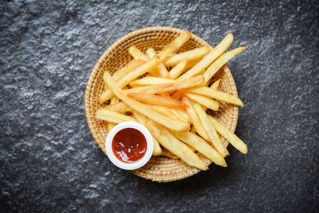 French fries on basket with ketchup on dark
