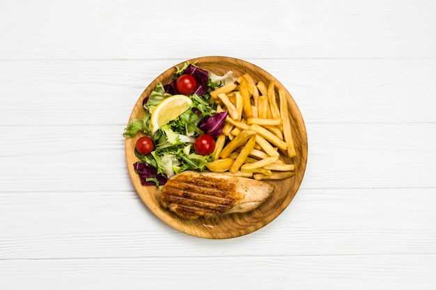 French fries and chicken with salad