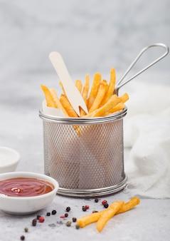 가벼운 탁자 배경에 소금과 토마토 케첩이 든 스트레이너 바구니에 감자 튀김 칩.