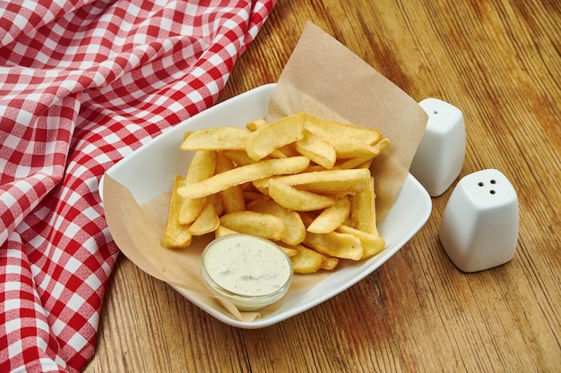 French fries in craft paper on gray plate on wood. american traditional fast food.